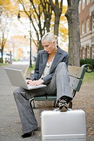 Young blonde woman using laptop on bench in neighborhood