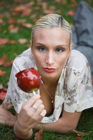 Portrait of young blonde woman holding candy apple on grass