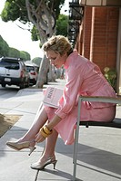 Young woman in pink dress adjusting shoe on sidewalk.