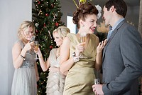 Portrait of couple and friends socializing with drinks at Christmas party