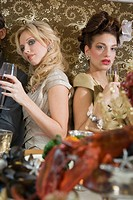 Two sexy women at dinner party sitting at table drinking wine