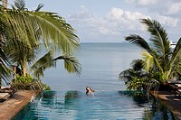 Thailand, Koh Samui. Thai Woman bathing in swimming pool next to sea                                                                                  ...