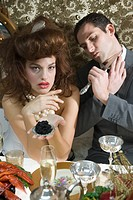 Portrait of sullen woman holding caviar at elegant dinner party, man shaving with knife beside her