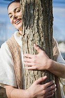 Smiling young woman hugging tree trunk