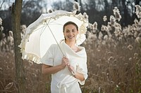 Smiling young woman with a white umbrella in a field