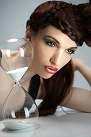 Portrait of sexy woman with retro hairstyle sitting with hourglass, studio shot