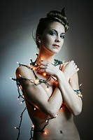 Portrait of sexy nude woman wrapped in Christmas lights, studio shot