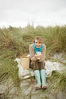 Woman sitting on dune with hot drink