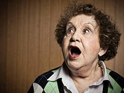 Studio portrait of shocked senior woman