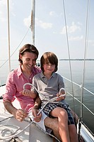 Father and son on board yacht holding rope (thumbnail)