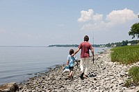 Father and son walking along beach with fishing rods (thumbnail)