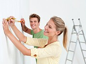 Young couple using measuring tape on wall (thumbnail)