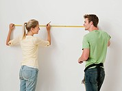 Young couple using measuring tape on wall