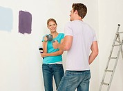 Young couple looking at paint on wall (thumbnail)