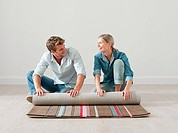 Young couple unrolling rug on floor