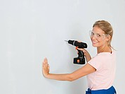 Young woman using electric drill