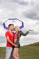 Young couple under umbrella, testing for rain (thumbnail)