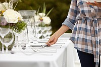 Woman preparing table for dinner party in a field (thumbnail)
