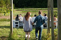 Couple arriving at dinner party on farm