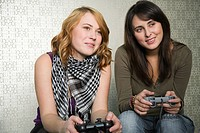 Teenage girls playing on games console