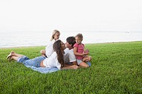 Family relaxing on grass by the sea