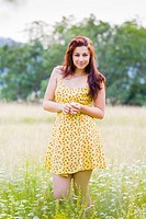 Pretty in a flowery dress young woman in a field