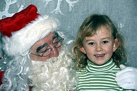 Little girl with Santa Claus in his grotto at Motcombe Infants School, Eastbourne, East Sussex, England