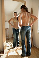 Woman in front of mirror trying on jeans