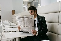 Young man sitting in a cafe eading newspaper
