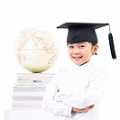 girl wearing graduation hat in front of book and globe