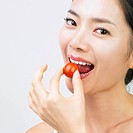 a womans face eating a small tomato