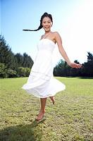 a woman running grass field with bare feet