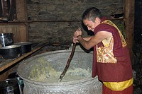 A monk stirs a pot of tsampa barley, the staple of the Tibetan diet, Katok Dorjeden Monastery _ Kham, Tibet, Sichuan, China