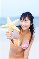 a woman holding a starfish in the seaside