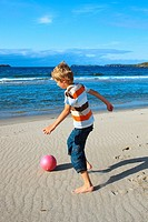 boy playing football on beach, Sutherland, Scotland