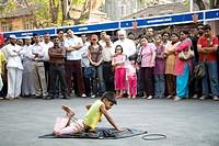 12 years old boy passing his body through iron ring audience watching performing in Kala ghoda festival annual art fair , Bombay Mumbai , Maharashtra ...