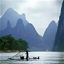 fisherman punting and cormorants standing on raft in Lijiang River and fog in mountains,Guilin,Guangxi,china