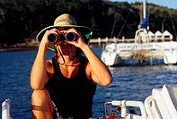 Australia, Queensland, Whitsunday Islands, Man with binoculars on a boat in front of Lindeman island