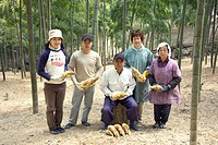 Farmer family holding bamboo shoots