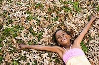 Girl 8_9 lying back in pile of autumn leaves, smiling