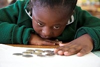 Close up shot of young schoolgirl counting coins, KwaZulu Natal Province, South Africa