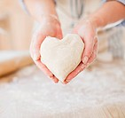 Close up of woman holding heart_shape dough