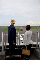 Senior couple looking at airplane at airport