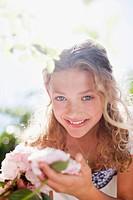 Smiling girl touching pink flowers