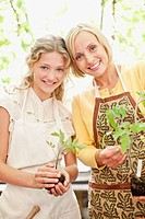 Smiling mother and daughter in aprons holding seedlings