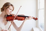 Woman playing violin near window