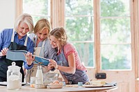 Multi_generation females looking at cookbook and baking in kitchen
