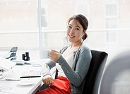 Smiling businesswoman drinking coffee at desk in office