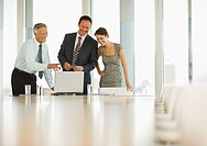 Smiling business people looking at laptop in conference room