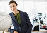 Smiling businesswoman next to globe in office